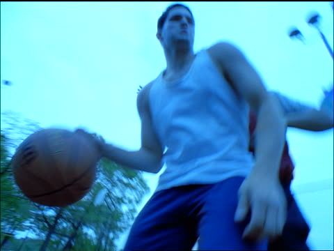 SLO MO CU Men playing basketball outdoors / one man shooting basket and scoring