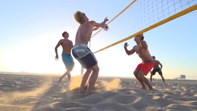men playing beach volleyball. - slow motion - filmed at 240 fps - volleyballnetz stock-videos und b-roll-filmmaterial