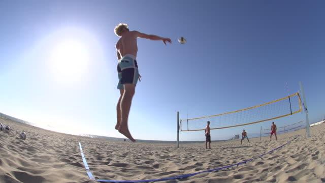 Men playing beach volleyball.
