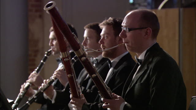 ms men playing clarinets and bassoons in orchestra / london, united kingdom - fyra människor bildbanksvideor och videomaterial från bakom kulisserna