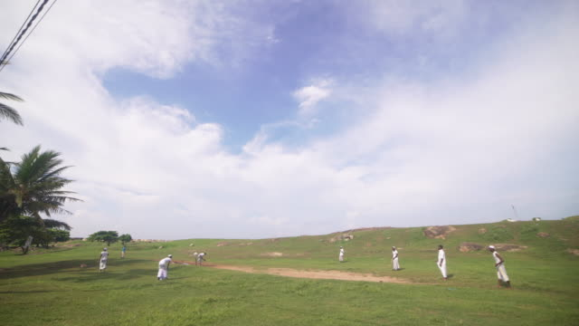 men playing cricket at green field of galle, sri lanka - sri lankan culture stock videos & royalty-free footage
