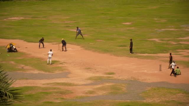 men playing cricket on dirt pitch at park in galle - jugendmannschaft stock-videos und b-roll-filmmaterial