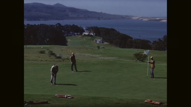 WS Men playing golf with sea in background / United States