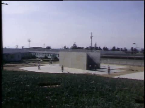 1968 MONTAGE Men playing handball in outdoor court at a prison