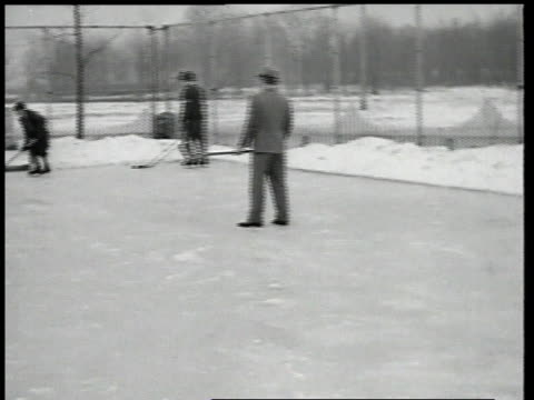 1937 WS Men playing ice hockey in suits as little girl ice skates by / Michigan, United States
