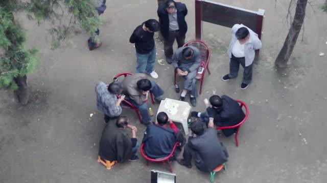 ha ms men playing poker in park/xian,shaanxi,china - poker card game stock videos & royalty-free footage