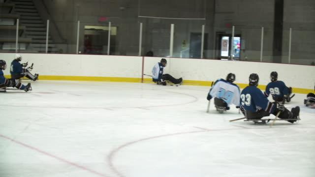 Men playing sledge hockey (sled hockey)
