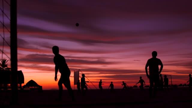 men playing soccer football on the beach of a tropical island at sunset. - slow motion - fotboll lagsport bildbanksvideor och videomaterial från bakom kulisserna