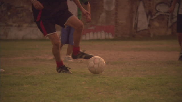 SLO MO, PAN, MS, men playing soccer on field at sunset, Buenos Aires, Argentina