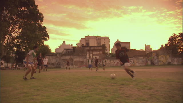 SLO MO, PAN, WS, men playing soccer on field at sunset, Buenos Aires, Argentina