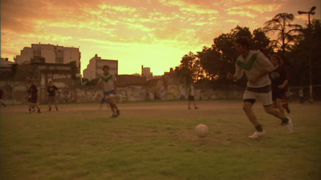 vidéos et rushes de slo mo, pan, ms, men playing soccer on field at sunset, buenos aires, argentina - argentina