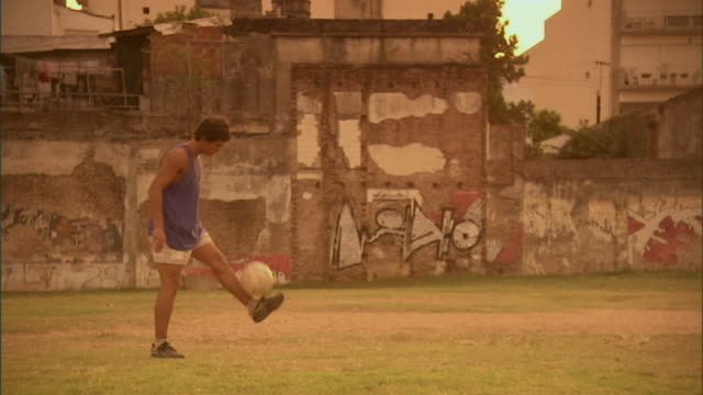 vidéos et rushes de slo mo, pan, ws, men playing soccer on field at sunset, buenos aires, argentina - argentine