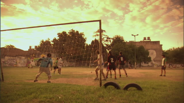 SLO MO, WS, PAN, men playing soccer on field at sunset, Buenos Aires, Argentina