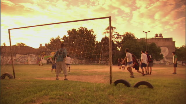 vidéos et rushes de slo mo, ws, pan, men playing soccer on field at sunset, buenos aires, argentina - argentine