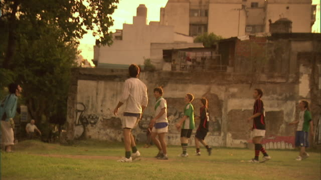 SLO MO, MS, ZO, men playing soccer on field at sunset, Buenos Aires, Argentina