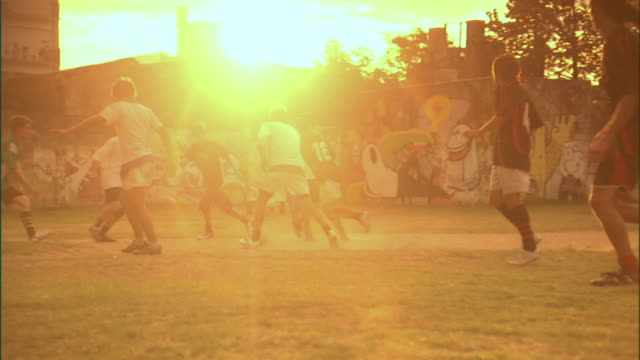 slo mo, ms, pan, men playing soccer on field at sunset, buenos aires, argentina - argentina stock-videos und b-roll-filmmaterial
