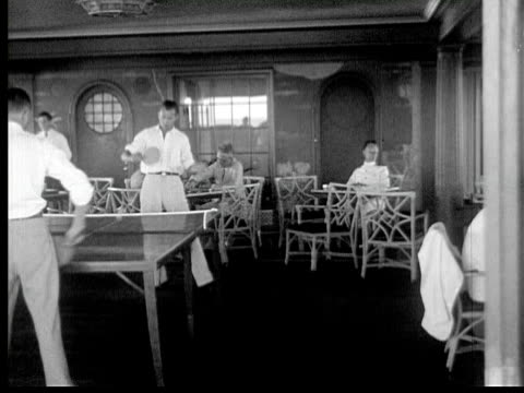 1934 B/W MONTAGE LA MS PAN HA WS Men playing table tennis in recreation room, people relaxing and drinking at tables, men standing at bar counter on board of cruise ship / Gulf of Mexico
