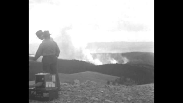 men pointing to smoke from forest fire far in the distance; close view of radio operator wearing headphones with table-top equipment / note: exact... - table top view stock videos & royalty-free footage