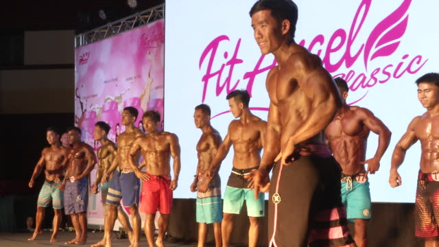 Men pose during the Fit Angel Classic bodybuilding competition in Bangkok Thailand