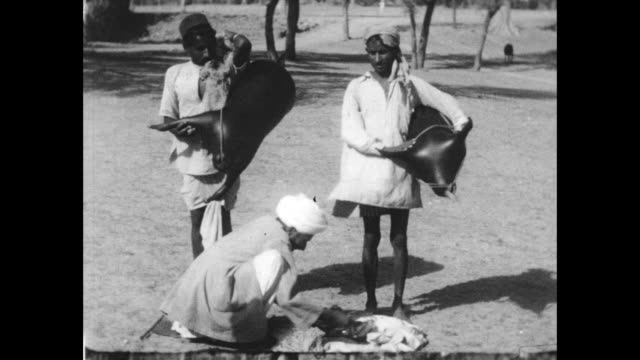 men pose with inflated animal skins, used for carrying water or as floating transport. - colonial stock videos & royalty-free footage