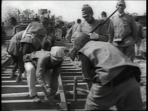 vídeos y material grabado en eventos de stock de men pounding in stakes / soldier with gun watching workers pounding spikes into railroad track - 1938