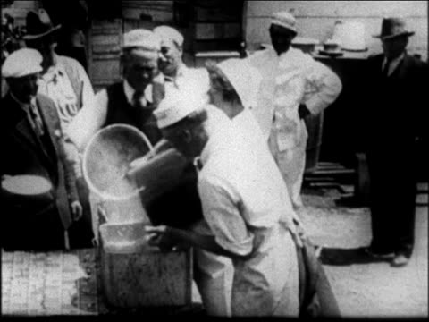b/w 1931 men pouring pots of stew into containers mother jordan starts serving at soup kitchen - 1931 stock videos & royalty-free footage