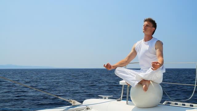 HD: Men Practicing Yoga On The Ocean