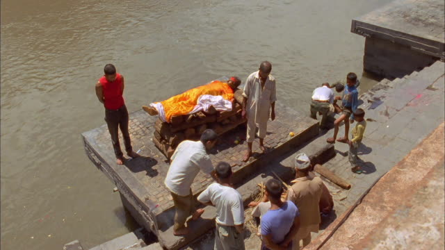 Men prepare a body on a funeral pyre for cremation. Available in HD.