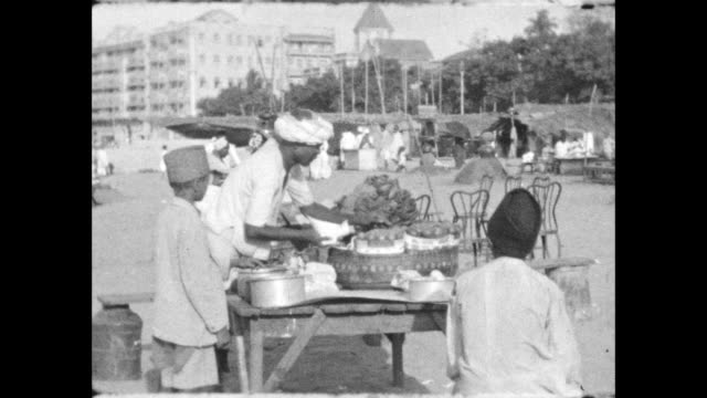 men preparing fishing boats and nets on a beach outdoor food and tea vendors on the beach - colonial stock-videos und b-roll-filmmaterial
