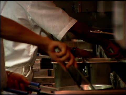 vídeos de stock e filmes b-roll de men preparing food in kitchen - só homens de idade mediana