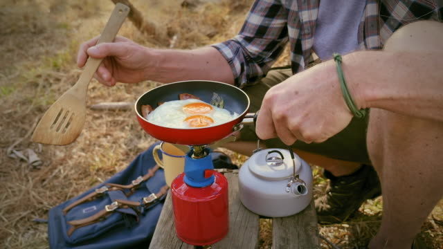 men preparing fried egg - camping stove stock videos and b-roll footage
