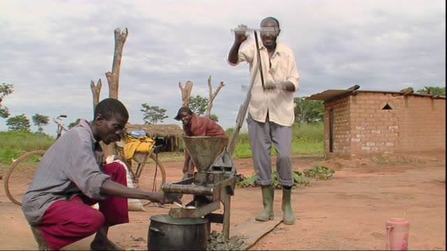 ws men preparing oil with using old fashioned sunflower press / mpika, zambia - essential oil stock videos & royalty-free footage