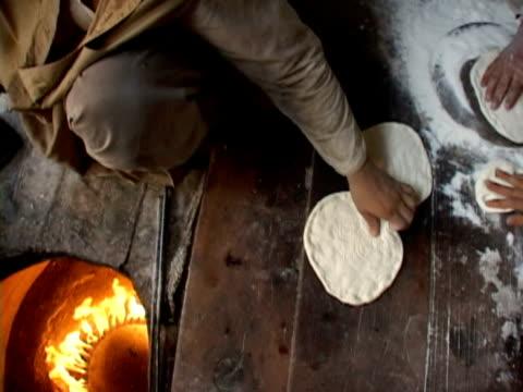 vidéos et rushes de cs, ha men preparing pastry and putting into stove, kabul city, kabul, afghanistan - plan grue
