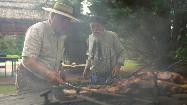 vídeos y material grabado en eventos de stock de hombres preparando el costillar para cocinar leña - argentina