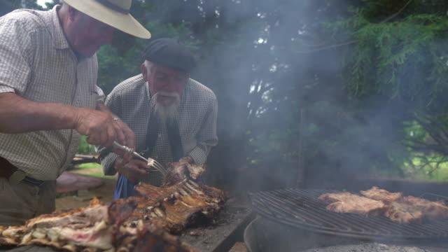 vídeos de stock e filmes b-roll de men preparing the costillar for firewood cooking - gaúcho