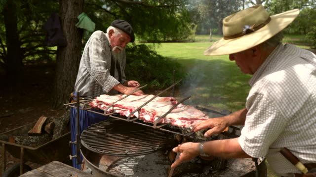 men preparing the costillar for firewood cooking - smoked stock videos & royalty-free footage