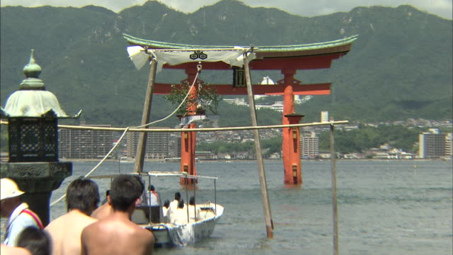 Men pull a rope to transport a pot to the Itsukushima Shrine.