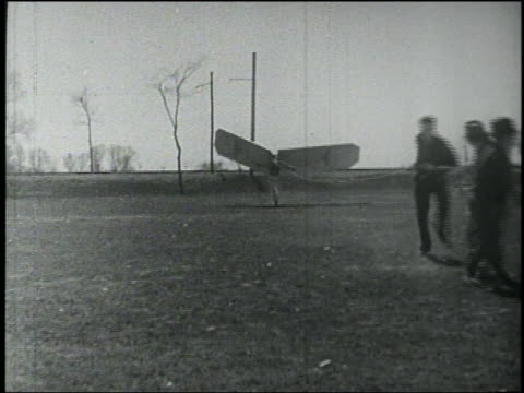 b/w men pull rope attached to man with wings on back who falls to ground - air vehicle stock videos & royalty-free footage