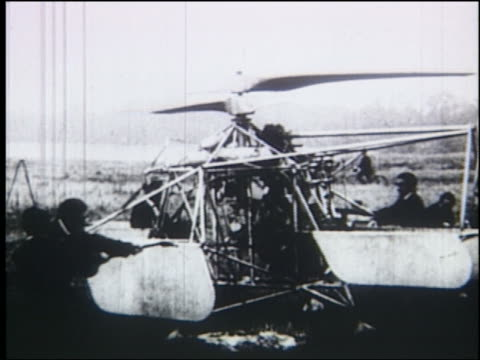 b/w men pull straps to start rotor of early helicopter - hubschrauber stock-videos und b-roll-filmmaterial