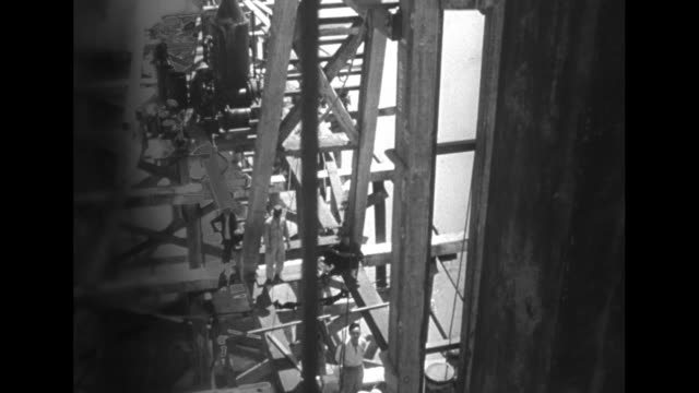 vídeos de stock, filmes e b-roll de men pulling a large wooden plank and several shots of a piledriver in action during reconstruction of the yellow river dam / men hammering on an... - pile driver