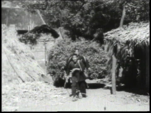 1938 ws men pulling and pushing cart loaded with brush up a village street / china - pferdekarre stock-videos und b-roll-filmmaterial