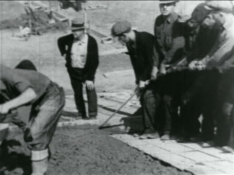 b/w 1934 men pulling rake to level cement on hillside in wpa construction project / documentary - new deal video stock e b–roll