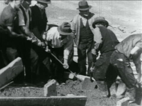 B/W 1934 men pulling rake to level cement on hillside in WPA construction project / documentary