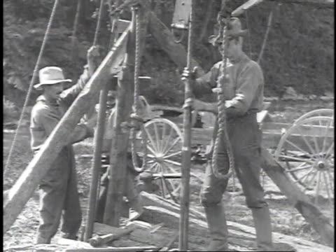 1923 reenactment men pulling ropes drilling for oil / titusville, pennsylvania, united states  - 1923年点の映像素材/bロール