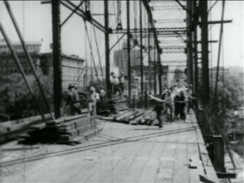 B/W 1934 men pulling something on bridge under construction by WPA / documentary