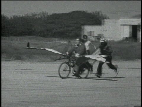 b/w men push man on bicycle with wings + tail / 1 man lights engine, bicycle wipes out burning - air vehicle stock-videos und b-roll-filmmaterial