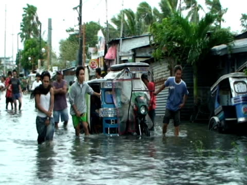 men push stalled motorbike out of flooded street in cupang in aftermath of typhoon mirinae, philippines, 2009 - 強風点の映像素材/bロール
