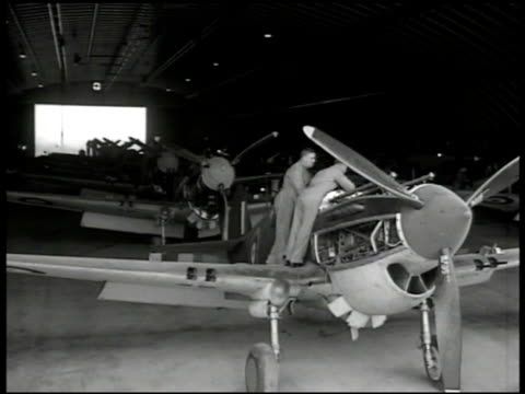 Men pushing airplane engine on cart VS Mechanics working on rows of fighter airplanes MS Crane moving propellers into place CU British woman working...