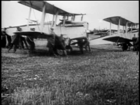 b/w 1918 men pushing dh4 airplane onto airfield - aereo militare video stock e b–roll