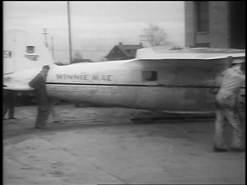 "men pushing ""winnie mae"" prop plane into hangar / cleveland, oh / newsreel - 1935 stock videos & royalty-free footage"